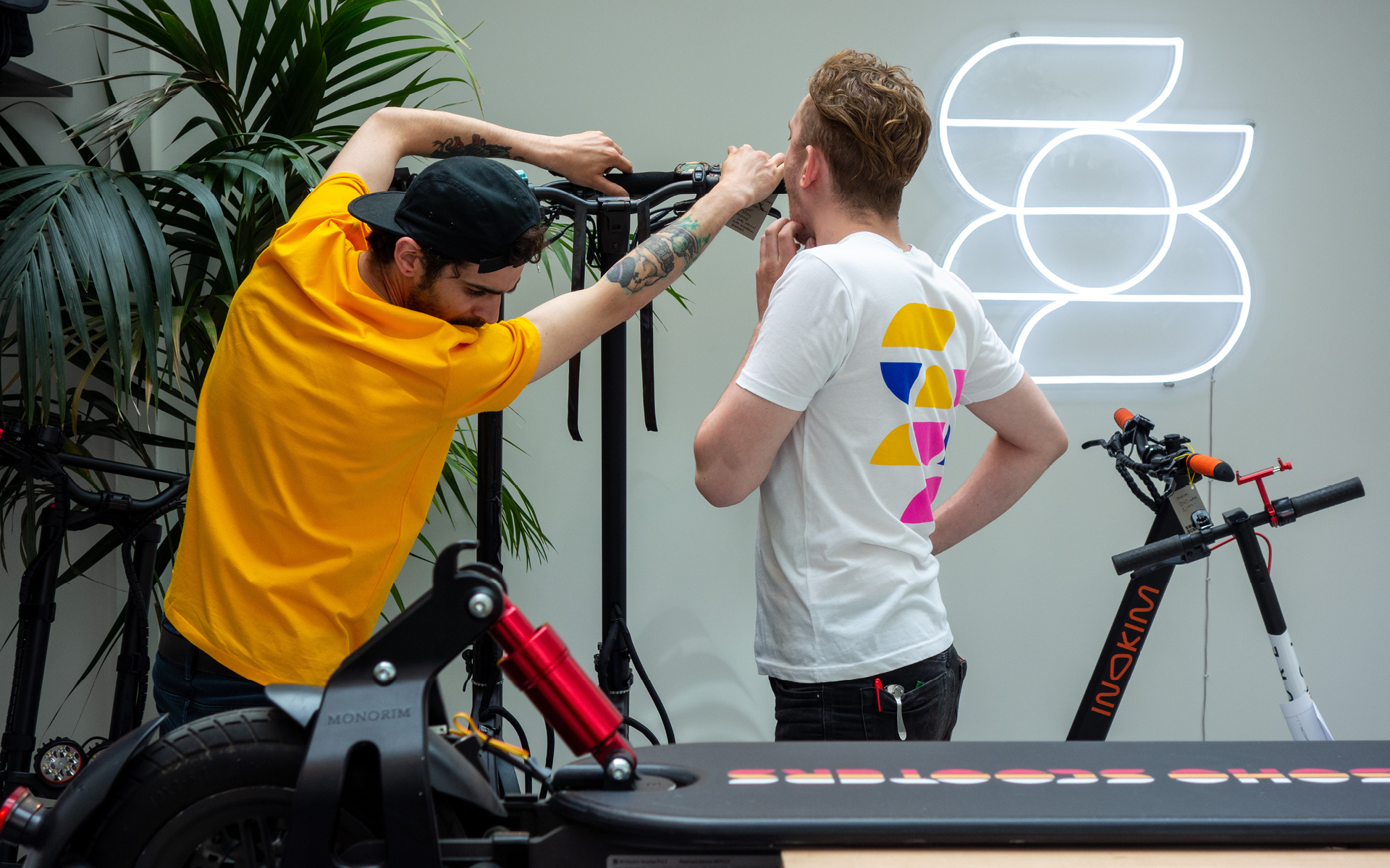 Soho Scooters engineers displaying branded merchandise and workshop